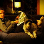 woman reading a magazin laying on the couch with her dog
