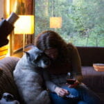 woman holding a glass of red wine next to her dog