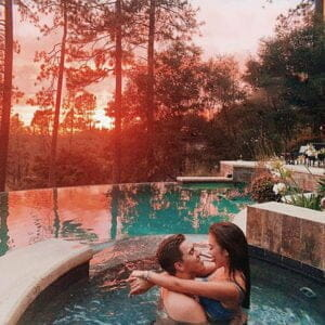 a couple of influencers hugging each other in the hut tub in the middle of the woods