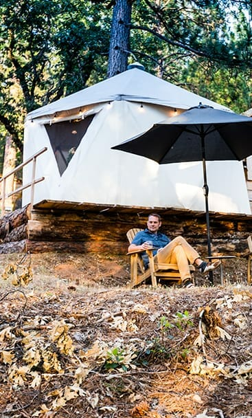 a man sitting on an outdoor chair in front of yurt ponderosa