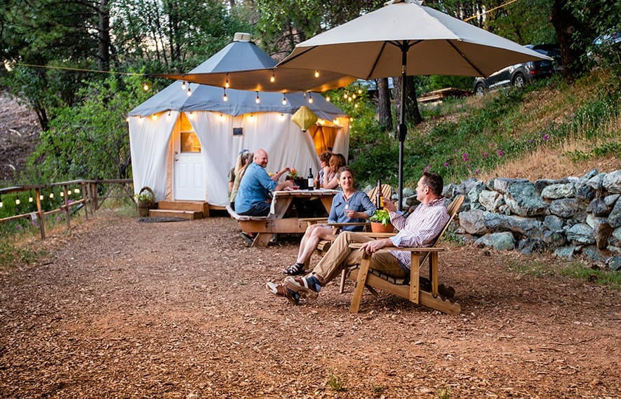 reverie retreat outdoors dinning table surrounded by a group of six people having beer and wine