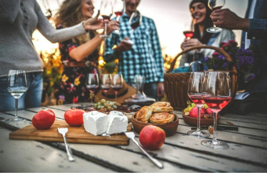 picnic table with glasses of red wine, cheese, fruits and other snacks surrounded by a group of friends